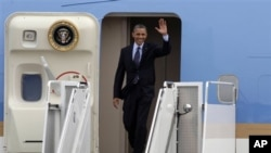 President Barack Obama waves upon arrival to Cartagena, Colombia, April 13, 2012.
