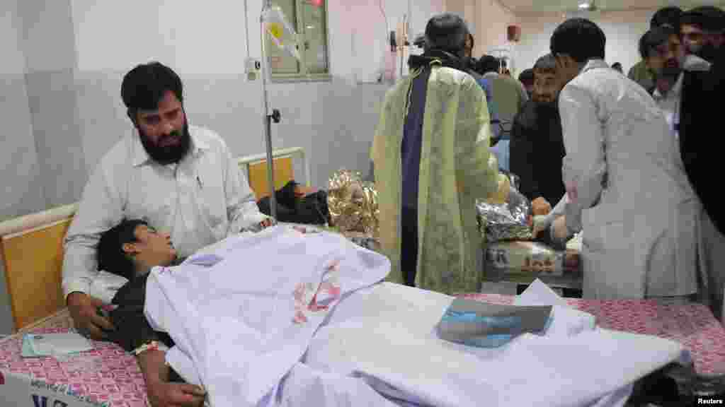A man comforts his son, who was injured during an attack by Taliban gunmen on the Army Public School, at Lady Reading Hospital in Peshawar, Pakistan, Dec. 16, 2014.