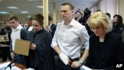 Pemimpin oposisi Rusia Alexey Navalny (dua dari kanan) berdiri saat mendengarkan keputusan hakim di pengadilan Kirov, Rusia (17/4).