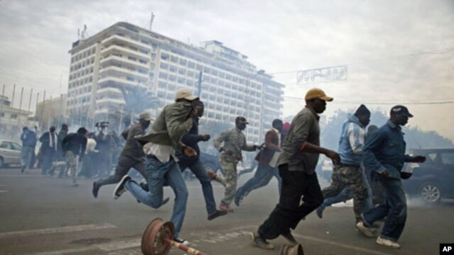 Anti-government protestors run from tear gas in Senegal's capital Dakar, February 15, 2012.