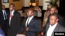 Picha ya Maktaba; rais wa Burundi Pierre Nkurunziza, katikati, akisindikizwa katika uwanja a ndege wa kimataifa wa Julius Nyerere International Airport, jinini Dar es Salaam, Tanzania, Mei 13, 2015.