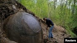 Suad Keserovic cleans a stone ball in Podubravlje village near Zavidovici, Bosnia and Herzegovina, April 11, 2016.