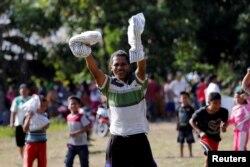 Čovek drži potrepštine nakon što je helikopter indonežanskog Crvenog krsta izbacio pomoć na zemljotresom pogođenu oblast Sirenja, namesništvo Dongala, celtranki Sulavesi, Indonezija, 5. okotbra 2018.