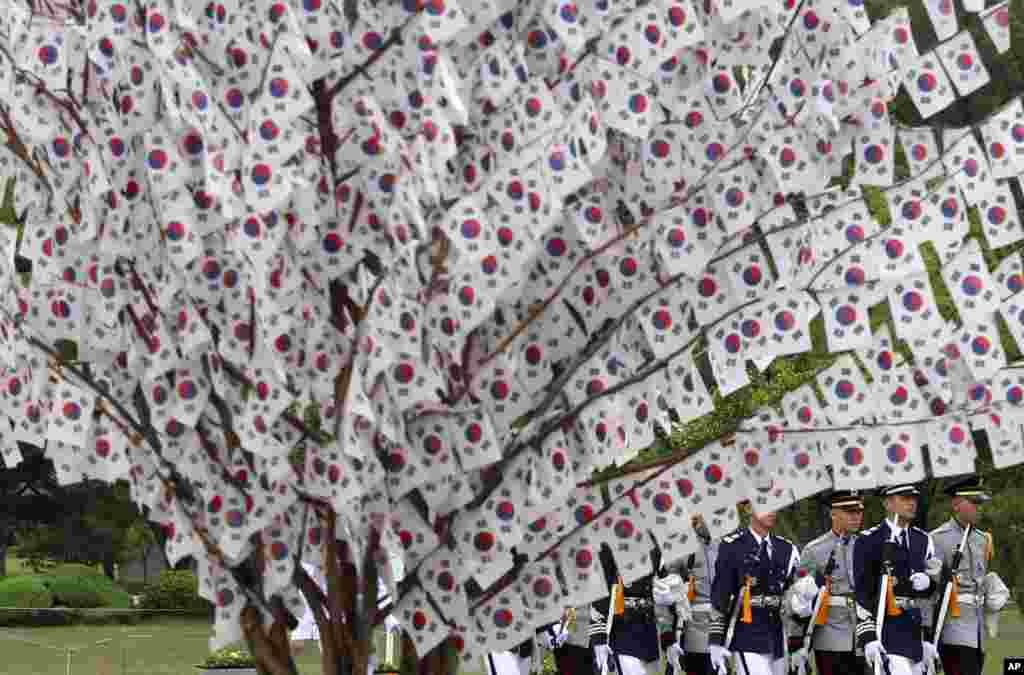 Các binh sĩ Nam Triều Tiên đi ngang qua các lá quốc kỳ được treo trên các cành cây để kỷ niệm ngày Chiến sĩ Trận vong 6 tháng 6 tại Nghĩa trang Quốc gia Seoul.
