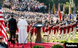 "U.S. President Barack Obama, left, and Pope Francis watch onstage as the ""Old Guard"" fife and drum corps marches past during an official welcome ceremony on the South Lawn at the White House in Washington, Sept. 23, 2015."