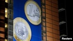 Spanduk yang menunjukkan gambar koin Euro Latvia dipasang di depan markas besar Komisi Eropa di Brussels (20/12). (Reuters/Francois Lenoir)