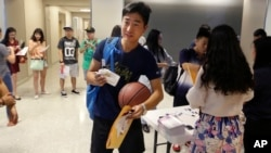 FILE - Weikang Nie, a finance graduate student from China, walks into an orientation for Chinese students at the University of Texas at Dallas in Richardson, Texas, Aug. 22, 2015.