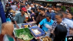 "Office workers shop for ""iftar,"" the meal to break their fast on the first day of the holy fasting month of Ramadan, at the main business district in Jakarta, Indonesia, June 18, 2015."