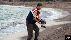 Sĩ quan cảnh sát bế thi thể bé Aylan 3 tuổi bị chết đuối và trôi dạt vào bờ biển Thổ Nhĩ Kỳ.