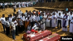 People react during a mass burial of victims, two days after a string of suicide bomb attacks on Easter Sunday, at a cemetery near St. Sebastian Church in Negombo, Sri Lanka, April 23, 2019. (REUTERS/Athit Perawongmetha)