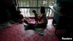 FILE - Aey, a 20-year old mother of three, holds her son at their home in a Bangkok's slum October 7, 2012.