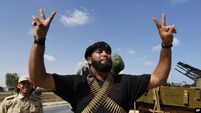 A member of the forces loyal to Libya's interim rulers flashes the victory sign as he prepares for an assault on Moammar Gaddafi's hometown Sirte September 24, 2011.