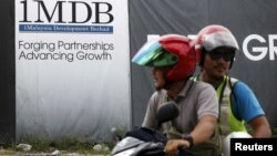 Pengendara motor melintas di depan papan iklan 1Malaysia Development Berhad (1MDB) di proyek pembangunan Tun Razak Exchange, di Kuala Lumpur, Malaysia, 3 Februari 2016