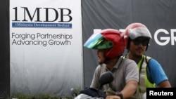 FILE - Motorcyclists pass a 1Malaysia Development Berhad (1MDB) billboard at the Tun Razak Exchange development in Kuala Lumpur, Malaysia, Feb. 3, 2016