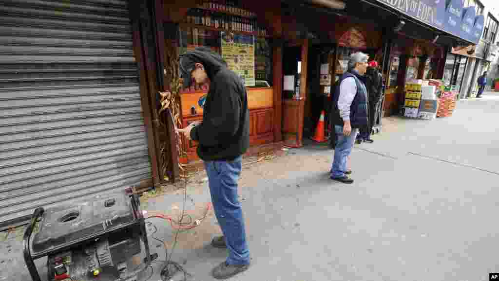A New York resident charges his cell phones from a generator connected to a 14th street market in the still powerless Chelsea section of Manhattan, New York, November 1, 2012.