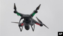FILE - A drone hovers over the scene of an explosion that leveled two apartment buildings in the East Harlem neighborhood of New York, March 12, 2014.