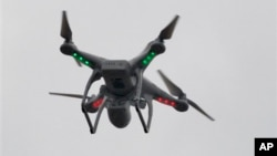 FILE - A drone hovers over the scene of an explosion that leveled two apartment buildings in the East Harlem neighborhood of New York, New York, March 12, 2014.
