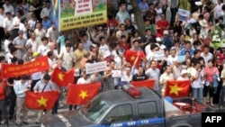 Một chiếc xe cảnh sát chạy ngang qua đoàn người biểu tình chống Trung Quốc ở Hà Nội, 7/8/2011