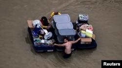 德克萨斯州休斯顿的居民带着个人物品在水中艰难前行(2017年8月30日)