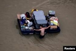 열대성 폭풍 '하비' 여파로 침수된 미국 텍사스주 휴스턴 주민들이 지난 30일 가재도구들을 챙겨 피신하고 있다.