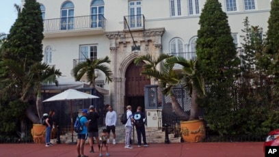 Tourists Pose For Photographs And Read A Restaurant Menu In Front Of The Villa Casa Casuarina