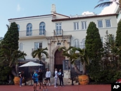 Tourists pose for photographs and read a restaurant menu in front of The Villa Casa Casuarina, a boutique hotel in Miami Beach, Fla.