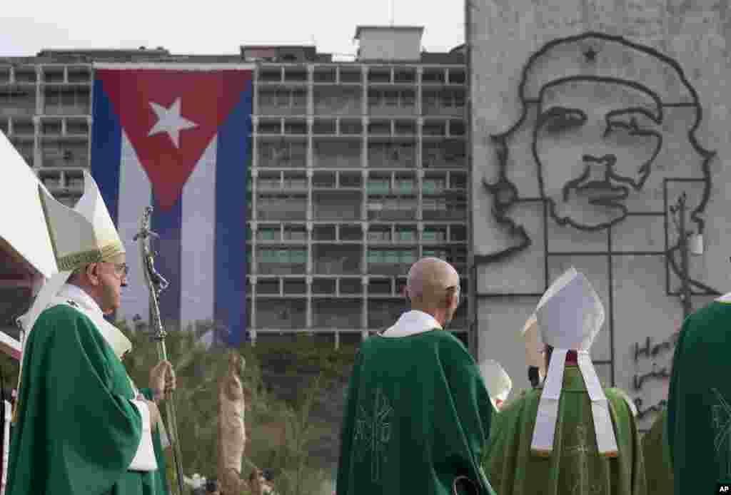 """Papa Francis awasili kuongoza Misa kwenye uwanja maarufu wa Mapinduzi Havana, akipeana uso na sanamu ya shuja wa mapinduzi Ernesto """"Che"""" Guevara na bendera ya Cuba iliyopambwa kwenye jengo la serikali, Sept. 20, 2015."""