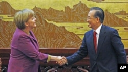 ນາຍົກລັດຖະມົນຕີເຢຍຣະມັນ ທ່ານນາງ Angela Merkel (ຊ້າຍ) ຈັບມືກັບນາຍົກລັດຖະມົນຕີຈີນ ທ່ານ Wen Jiabao ກ່ອນກອງປະຊຸມຖະແຫຼງຂ່າວທີ່ຫໍສາລາປະຊາຊົນໃນນະຄອນຫຼວງປັກກິ່ງ (2 ກຸມພາ 2012)