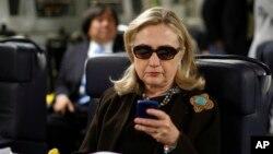 រូបឯកសារ៖ លោកស្រី Clinton ឆែកមើលទូរស័ព្ទរបស់លោកស្រីនៅក្នុងយន្តហោះយោធាកាលពីលោកស្រីនៅជារដ្ឋមន្ត្រីក្រសួងការបរទេសអាមេរិក។