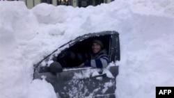 Một người lái xe ngồi trong chiếc xe của ông bị tuyết lấp đầy không thể di chuyển được