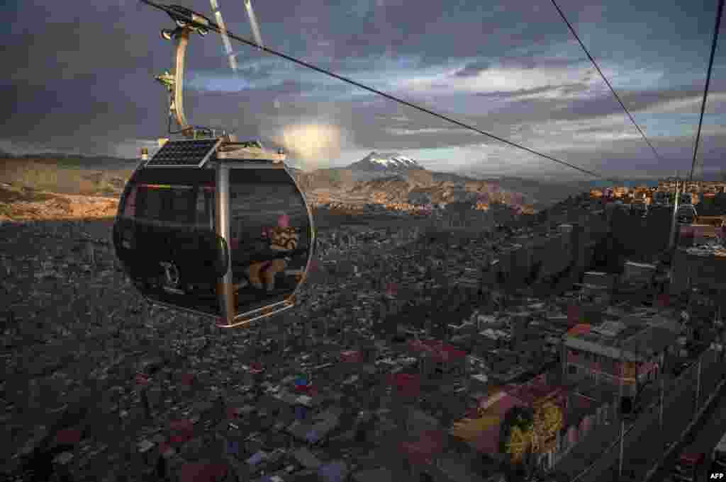 People ride a cable car, with La Paz and the Illimani mountain seen in the background, in El Alto, Bolivia, Oct. 17, 2019.