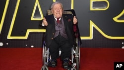 FILE - Britain Star Wars The Force Awakens Premiere: Kenny Baker poses for photographers upon arrival at the European premiere of the film 'Star Wars: The Force Awakens ' in London, Wednesday, Dec. 16, 2015.