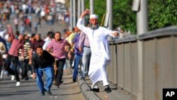 Man throws a stone during clashes between rival groups of protesters in Cairo, Egypt, Friday, April 19, 2013.