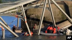 In this photo provided by Francisco Rodriguez, rescue boats approach victims at their vehicles in the Skagit River after the collapse of the Interstate 5 bridge in Mount Vernon, Wash., May 23, 2013.