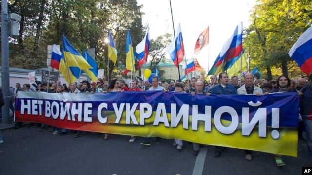 """Người biểu tình cầm băng-rôn viết """"không gây chiến với Ukraine"""" trong mộc cuộc biểu tình phản đối chiến tranh ở trung tâm Moscow, Nga, ngày 21 tháng 9, 2014."""