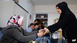 Une votante donne son vote dans un bureau à Istanbul, Turquie, le 16 avril 2017.