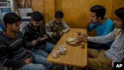 "Kashmiri students browse the internet on their mobile phones as they sits inside a restaurant in Srinagar, Indian controlled Kashmir, April 26, 2017. On Wednesday, authorities ordered internet service providers to block 16 social media sites, including Facebook and Twitter, and popular online chat applications for one month ""in the interest of maintenance of public order."""