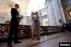 Sandy Stier (thứ 2 từ trái) và Kris Perry, nguyên đơn trong vụ kiện chống Dự luật 8, làm lễ cưới trước sự hiện diện của Bộ trưởng Tư pháp California Kamala Harris tại Tòa Thị Chính San Francisco, 28/6/ 2013.