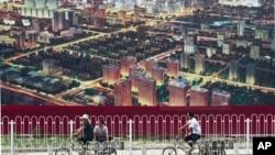 人们骑自行车经过北京一座广告牌,广告牌显示了北京中央商务区的景象(资料照片)