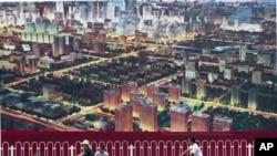 2011年7月人们骑自行车经过北京一座广告牌,广告牌显示了北京中央商务区的景象