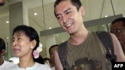 Bà Aung San Suu Kyi cầm tay con trai Kim Aris (phải) tại phi trường Quốc tế Yangon ngày 23/11/2010. Hai mẹ con bà Suu Kyi gặp lại nhau lần đầu tiên sau 10 năm xa cách