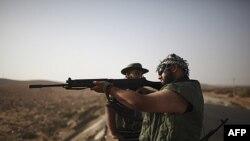 Chiến binh phe nổi dậy Libya tại một trạm kiểm soát đang kiểm tra một khẩu súng