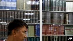 一中國人在北京一家書店走過展示中國百科全書的書櫃(2017年5月4日)