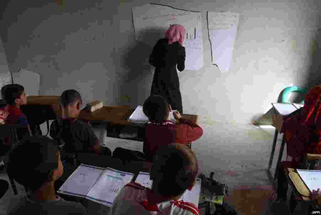 شام میں باغیوں کے زیر قبضہ شہر حریم میں ایک استانی ٹوٹے ہوئے بورڈ پر بچوں کے لیے سبق لکھ رہی ہے