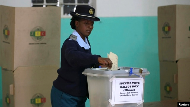 A member of the Zimbabwean police force casts her vote in the capital, Harare, July 14, 2013.
