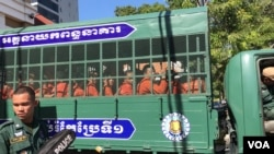 Prisoners wearing orange jumpsuits sit in a van en route from Prey Sar prison to the Phnom Penh Municipal Court, Cambodia, November 26, 2019. (Hul Reaksmey/VOA Khmer)