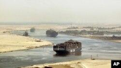 FILE - cargo ships sail through the Suez Canal near Ismailia, Egypt.