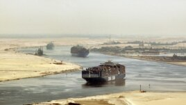 FILE - cargo ships sail through the Suez Canal near Ismailia, Egypt.