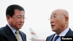 日本首相顾问饭岛勋(右)2013年5月14日抵达朝鲜平壤机场,朝鲜外务省亚洲事务部副主任金哲镐(左)在机场迎接。