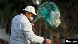 Petugas taman kota Shanghai menangkapi burung-burung merpati untuk mencegahnya merebaknya flu burung di sana (6/4).